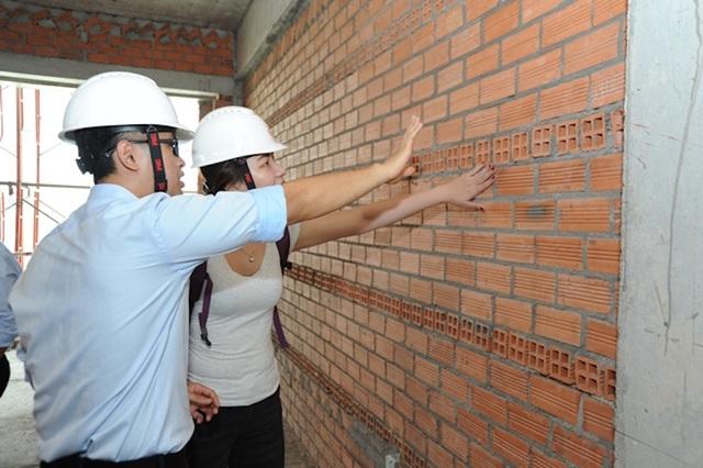 Khách hàng rất hứng khởi khi được nghe giải thích về quy chuẩn xây dựng và trực tiếp chạm vào từng hàng gạch thẳng tắp tại bước tường của mỗi căn hộ