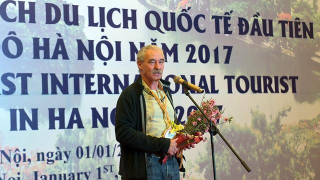 Ông Thomas Bauche xúc động khi trở thành vị khách du lịch quốc tế đầu tiên đến Thủ đô Hà Nội 2017. Ông cầm trên tay bó hoa đào tươi thắm.