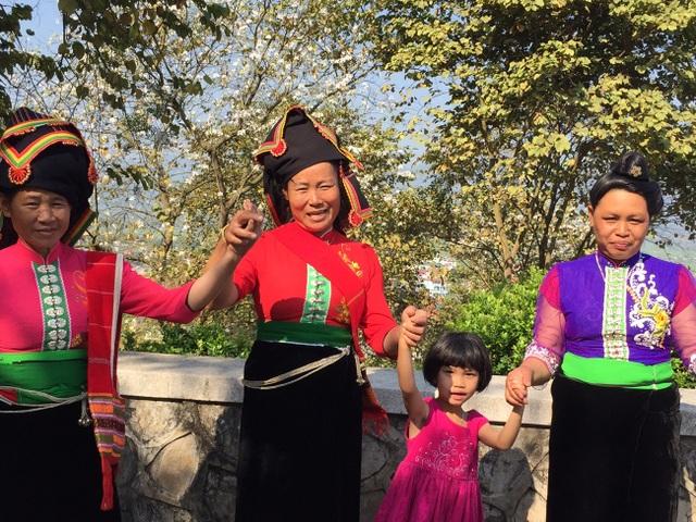 Bà con dân tộc Thái vui múa bên hoa ban trên đường lên Tượng đài Chiến thắng Điện Biên Phủ.