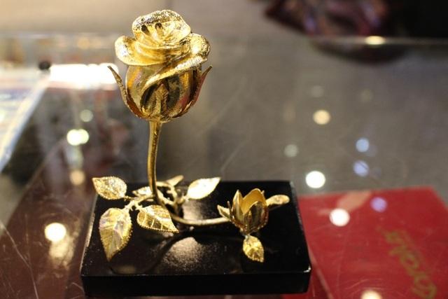 Hồng mạ vàng 3 trong 1 là mặt hàng được ra mắt vào đúng dịp 8-3. Bông hồng được thiết kế với những đường cong mềm mại của thân và lá tạo nên vẻ đẹp dịu dàng nhưng vẫn kiêu sa như người phụ nữ. Ngoài ý nghĩa trưng bày, bông hồng có thể được dùng làm giá cắm bút hoặc giá để card.