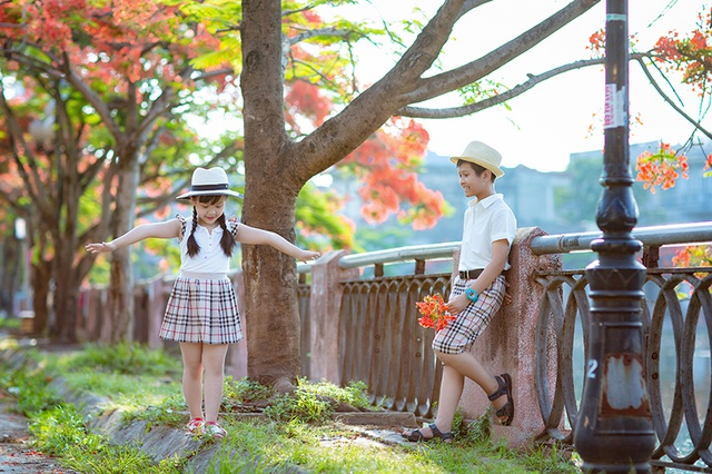 Cùng xem những hình ảnh đáng yêu của hai anh em Cộng Linh và Tuệ Minh trên con đường ngập hoa phượng đỏ của thành phố Hải Phòng