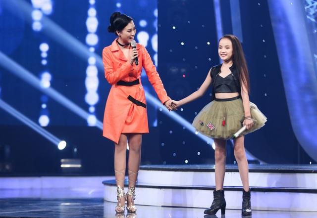 Trong Gala công bố Top 10, nữ MC nổi bật với trang phục cam trên sân khấu.