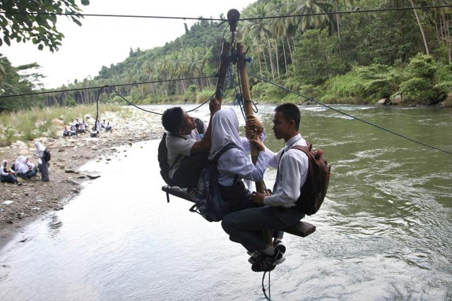 Trên đường từ trường về nhà ở làng Maroko, 3 học sinh buộc phải bám vào một ròng rọc tự chế để vượt qua con sông Ranteangin tại Kolaka Utara, Indonesia.
