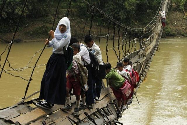 Các học sinh phải vượt sông bằng cách đi qua một cây cầu dây cũ kỹ để tới trường tại Lebak, Indonesia.