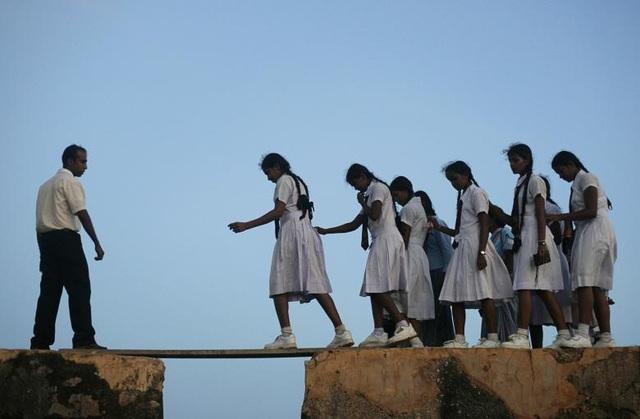 Các học sinh nữ bước qua một tấm ván gỗ trên đường tới trường ở Sri Lanka.