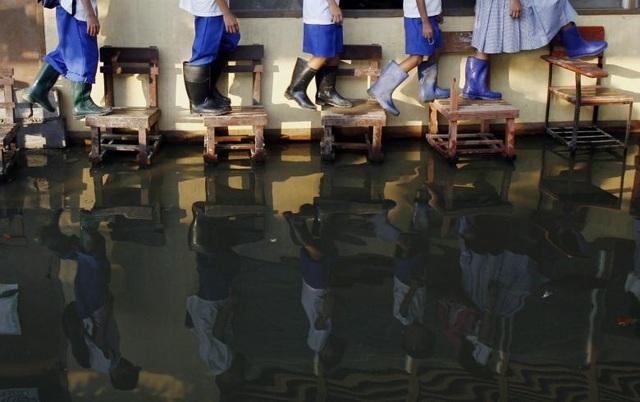 Các học sinh phải đi ủng cao su và bước lên những chiếc ghế để tới lớp tại trường tiểu học Sitio Tapayan ở Taytay, tỉnh Rizal, Philippines.