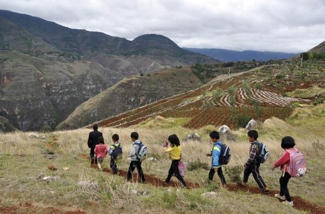 Thầy giáo Xie Bihua dẫn các học sinh từ trường về nhà ở khu vực đồi núi thuộc tỉnh Quý Châu, Trung Quốc.