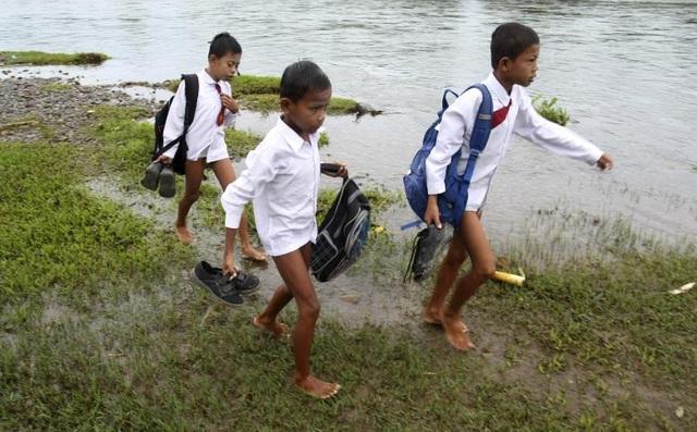 Các học sinh phải tháo quần dài và giày khi vượt qua sông để đến trường tại tỉnh West Sumatra ở Indonesia.