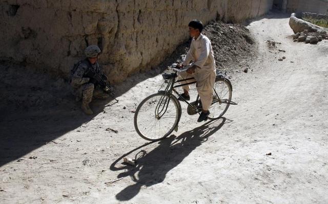 Một học sinh ở tỉnh Logar, Afghanistan đạp xe đi học trong khi một binh sĩ thuộc quân đội Mỹ cầm súng chiến đấu với phiến quân.