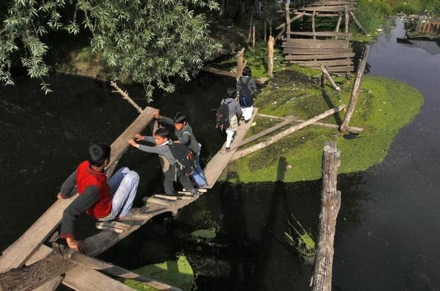 Học sinh Ấn Độ đi qua một cây cầu tạm ghép bằng những tấm gỗ trên đường từ trường về nhà.