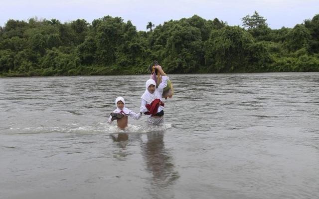 Các học sinh nữ lội qua sông tới trường ở tỉnh West Sumatra, Indonesia.