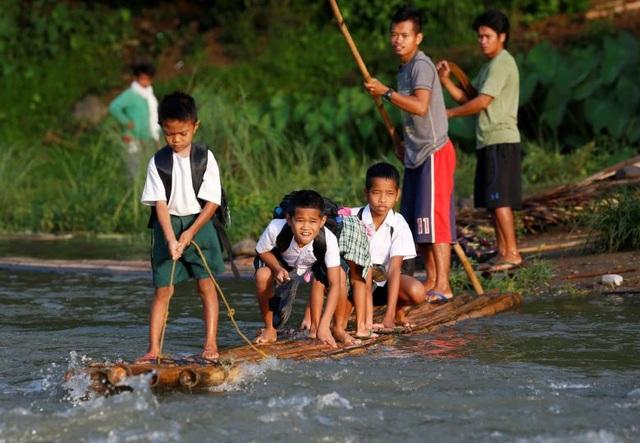 Các học sinh đứng trên một bè tự chế để vượt sông khi tới dự lễ khai giảng lớp học mới ở trường tiểu học Casili tại Montalban, Philippines.
