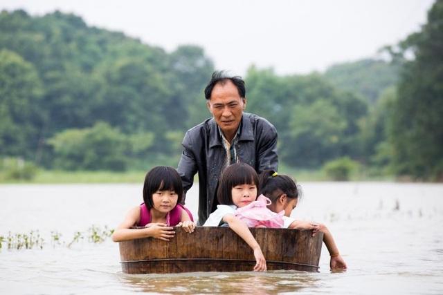 Một người đàn ông đẩy thùng gỗ chở 3 học sinh từ trường về nhà khi vượt qua vùng nước lũ ở Duchang, tỉnh Giang Tây, Trung Quốc.