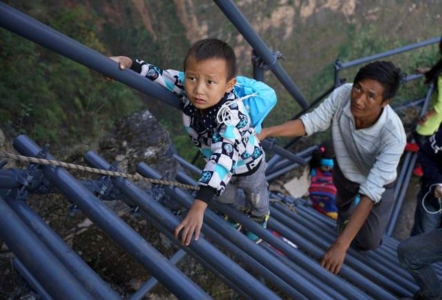 """Một học sinh sống ở """"làng vách núi"""" tại vùng Liangshan Sichuan, Trung Quốc phải leo lên các bậc thang bằng thép để đi học. Việc lắp đặt thang thép để thay thế chiếc thang cũ nguy hiểm đã giúp rút ngắn thời gian đi học của các học sinh trong vùng từ 3 giờ xuống 2 giờ đồng hồ."""