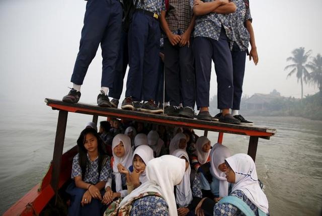 Do không đủ chỗ ngồi, các học sinh ở Palembang, đảo Sumatra, Indonesia thậm chí phải đứng trên nóc một thuyền gỗ khi vượt qua con sông Musi để đến trường học.