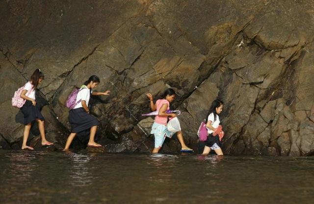 Các học sinh phải bám vào các tảng đá và đi men theo khu vực nước nông để đến trường tại làng Kawag, Subic, tỉnh Zambales, phía bắc thủ đô Manila, Philippines.