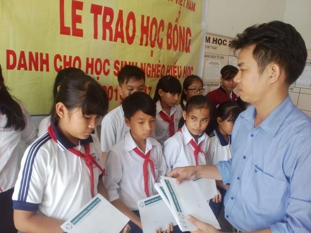 Ông Lê Kiếm Hoàng, trưởng đại diện khu vực TPHCM và Long An của Cty Grobest VN trao học bổng cho học sinh trường T iểu học Bình Phước.