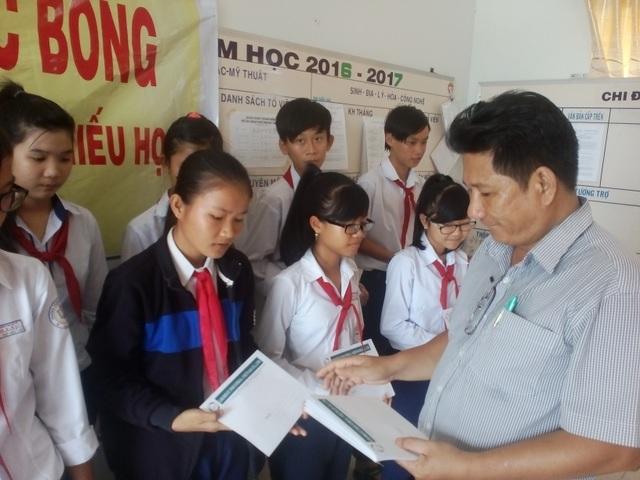 Thầy Võ Văn Mười, phó hiệu trưởng trường THCS Doi Lầu, trao học bổng cho các em học sinh.