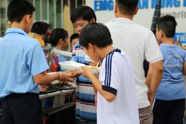 Một học sinh tranh thủ ăn vội trước giờ bước vào buổi học thêm
