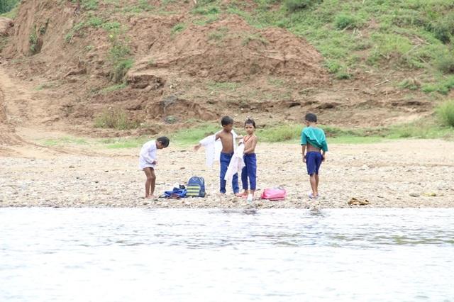 Nhóm học sinh mặc lại quần áo sau khi lội sông