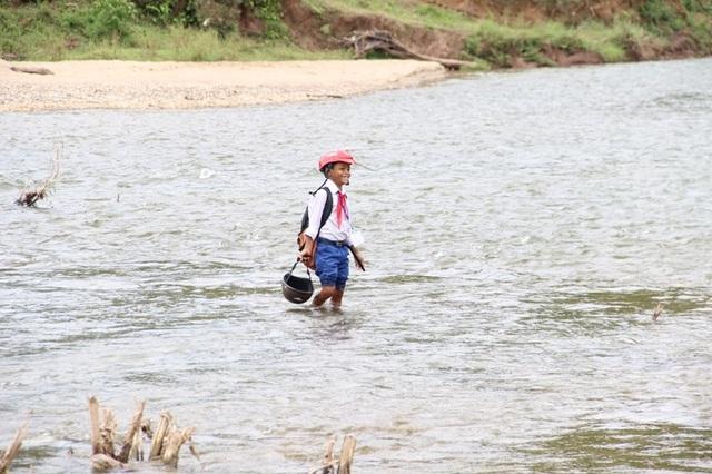 Một nam học sinh lội sông để đến trường