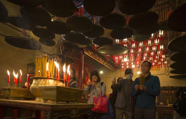 Người dân của nhiều nước châu Á thường đến những nơi thờ tự linh thiêng trong các ngày Tết để cầu xin những điều bình an và may mắn trong năm mới. Trong ảnh: người dân Hong Kong cầu khấn trong một ngồi đền (Ảnh: Reuters)