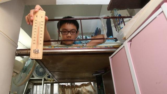 Một thiếu niên 13 tuổi giơ nhiệt kế cho thấy nhiệt độ bên trong căn buồng siêu nhỏ của cậu tại khu Sham Shui Po (Ảnh: SCMP)