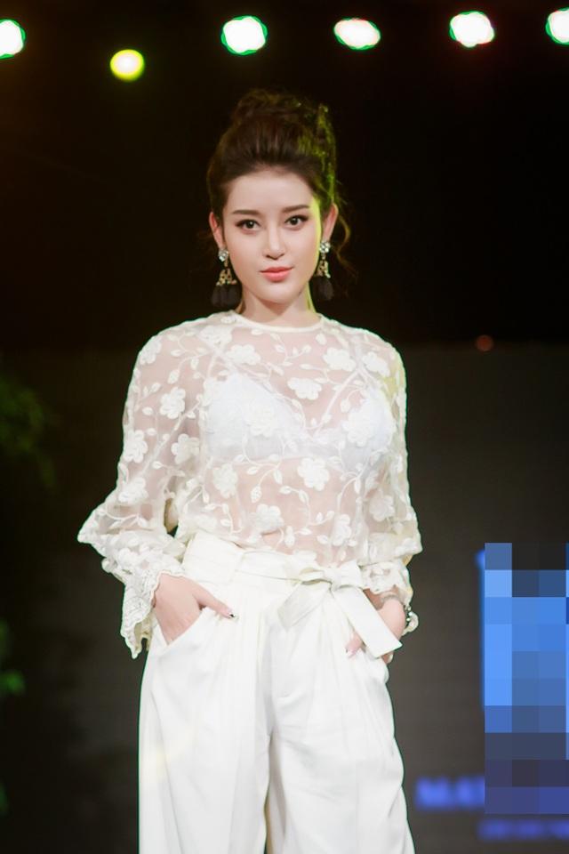 Á hậu Huyền My được giao cho vị trí vedette. Người đẹp diện cả cây trắng sành điệu với áo ren xuyên thấu nội y cùng quần suông rộng.