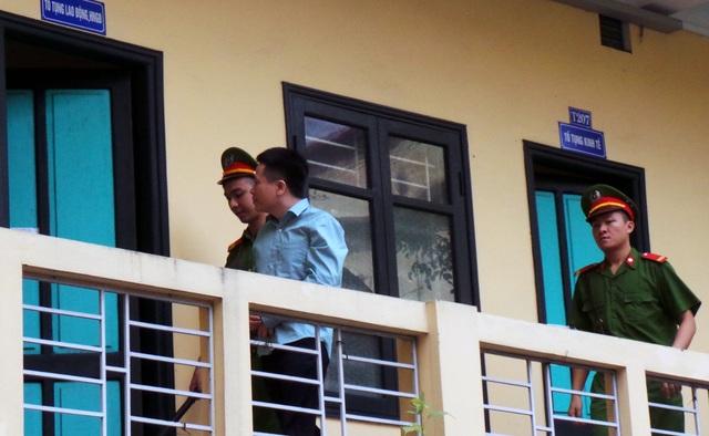 Hà Văn Thắm ngoái nhìn vào phòng giữ đồng phạm khi được đưa đến phòng xử.