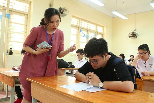 Giám thị nhắc nhở thì sinh về quy chế thi tại điểm thi trường THPT Việt Đức, Hà Nội. Ghi nhận trong buổi làm thủ tục dự thi ngày 21/6 (Ảnh: Mai Châm)