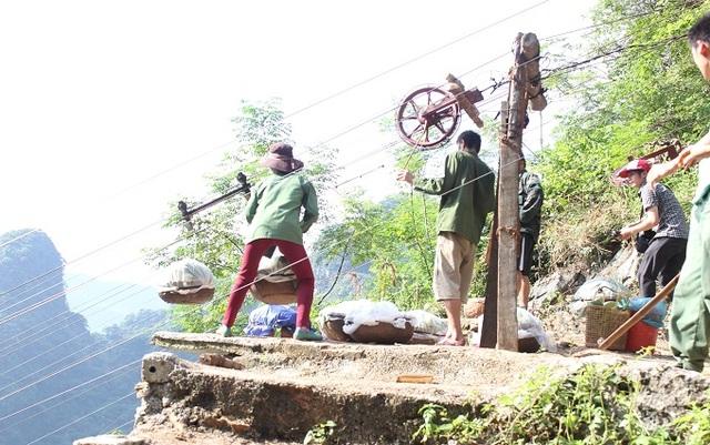 Chi chít những đường cáp. Na được người dân buộc vào cáp để thả xuống chân núi, có tay phanh để hãm tốc độ.