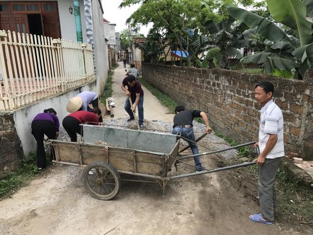 Người dân xã Đồng Tâm thu dọn cát đá đổ chắn lối ra vào ngõ xóm