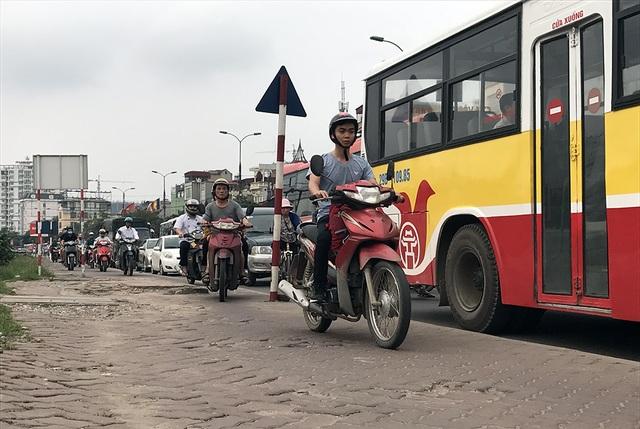 Nhiều người lao xe máy lên vỉa hè để tìm cách thoát khỏi cảnh ùn tắc kéo dài