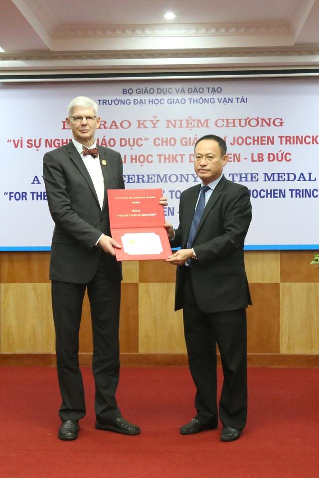 Vụ trưởng Vụ Quan hệ quốc tế Bộ GD&ĐT Nguyễn Xuân Vang đại diện Bộ GD&ĐT trao Kỷ niệm chương tới Giáo sư Jochen Trinckauf