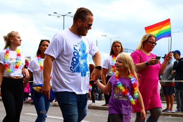 Một bé gái cùng bố hào hứng tham gia cuộc diễu hành trên phố.