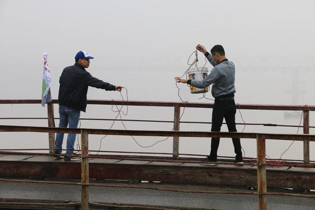 Từ trên cầu Long Biên, các bạn trẻ tình nguyện dùng dây để dòng xô xuống mặt sông, tránh việc thả cả rơi tự do trên cao.