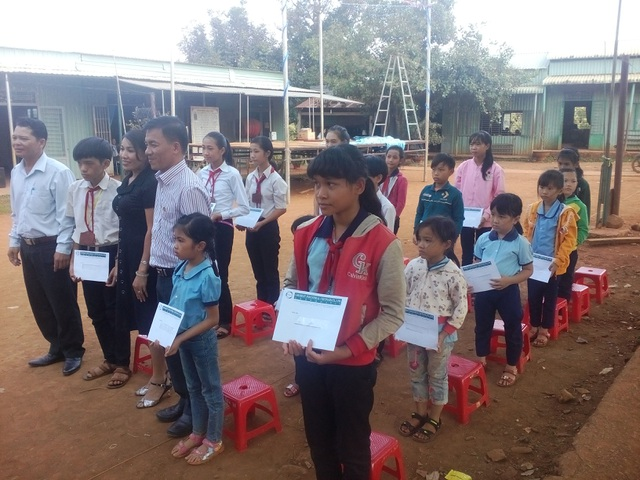 Các em học sinh trường Nguyễn Khuyến (huyện Bù Đăng) đón nhận học bổng.