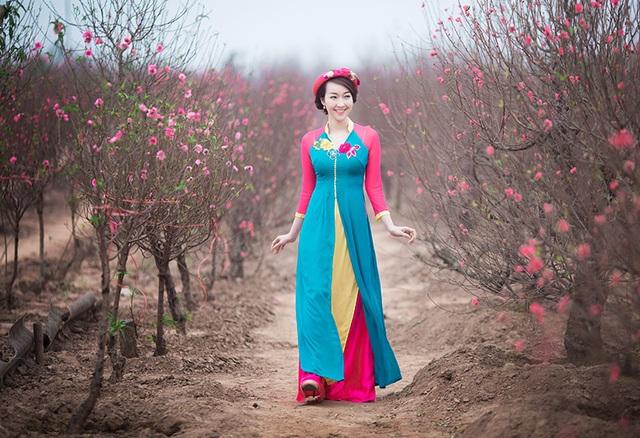 Bộ trang phục có thiết kế độc đáo và màu sắc tươi tắn của Trang Nhung khiến cô trở nên nổi bật giữa vườn đào Nhật Tân - nơi đang là địa điểm nóng thu hút các bạn trẻ ghé tới chụp ảnh trong những ngày giáp Tết.