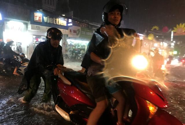 Một chiến sĩ Công an phường Linh Chiểu, quận Thủ Đức giúp đỡ người dân trên đường nước chảy siết.