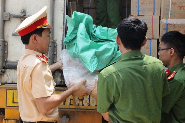 Cơ quan chức năng tiến hành bốc dỡ số thực phẩm bẩn được ngụy trang trong số hàng hóa có giấy tờ