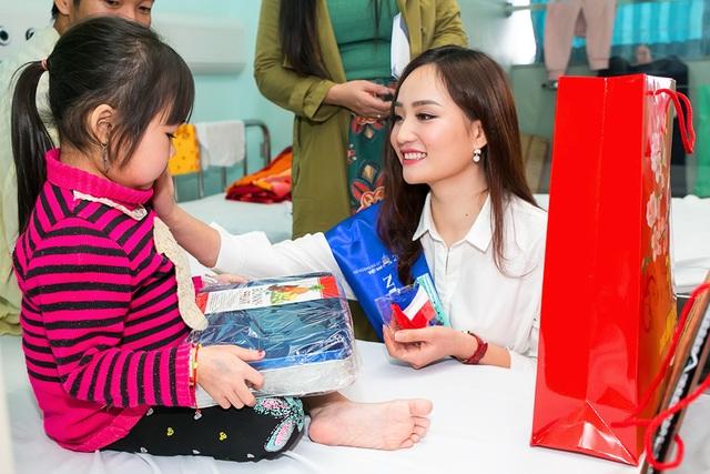 Bên cạnh việc trao quà, người đẹp còn động viên gia đình và các em nhỏ.