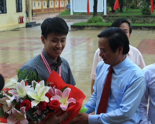 Giám đốc Sở GD&ĐT Quảng Bình Đinh Quý Nhân vui mừng ra đón và tặng hoa cho chàng trai vàng Trường THPT chuyên Võ Nguyên Giáp