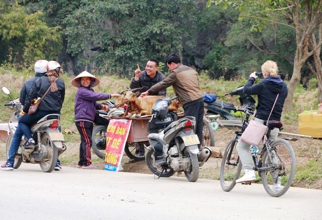 Một du khách nước ngoài dùng máy ảnh ghi lại cảnh bán thịt dê ven đường của người dân Ninh Bình