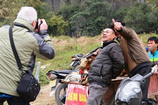Người bán thịt dê tạo dáng cho du khách chụp ảnh bên con dê bán thịt của mình