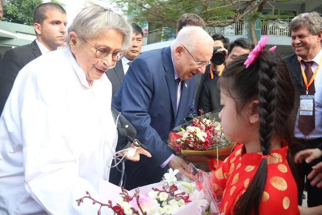 Tổng thống Rivlin và phu nhân đón nhận 2 đoá hoa tươi thắm của các em học sinh.