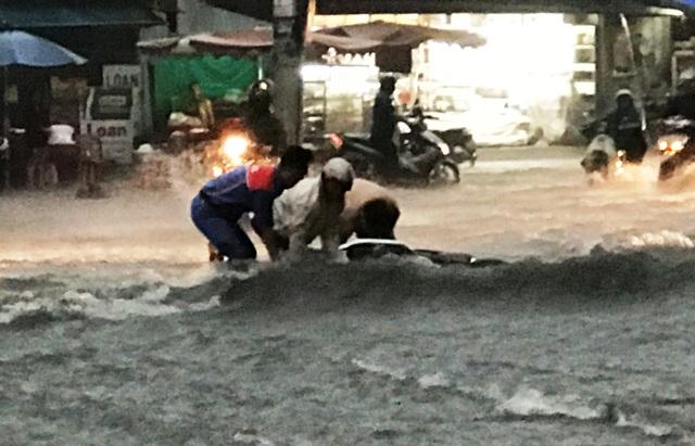 Nhiều người đi xe máy bị nước cuốn té ngã nhưng rất may được người dân địa phương hỗ trợ, cứu giúp.