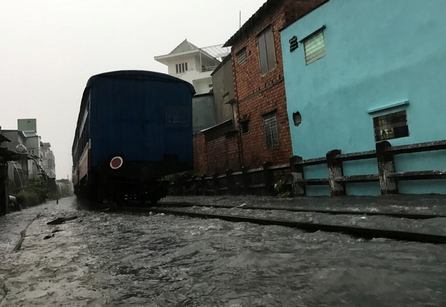 Đoàn tàu đi qua vùng ngập nước tại khu vực gác chắn Tô Ngọc Vân.