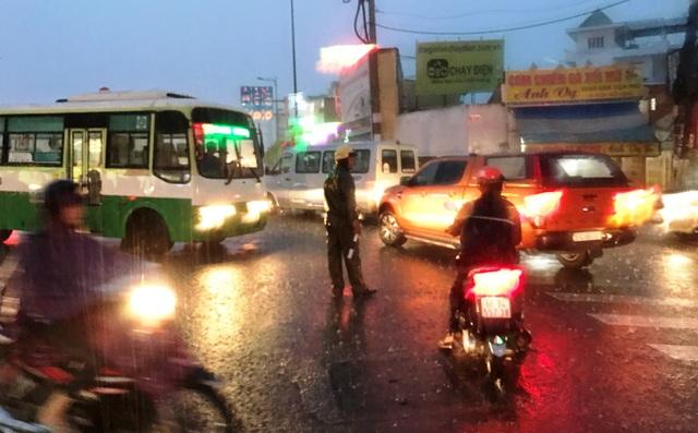 Cảnh sát giao thông thuộc Đội Tuần tra dẫn đoàn (PC67, Công an TPHCM) hướng dẫn phương tiện tìm hướng đi khác, tránh vào vùng ngập nước.