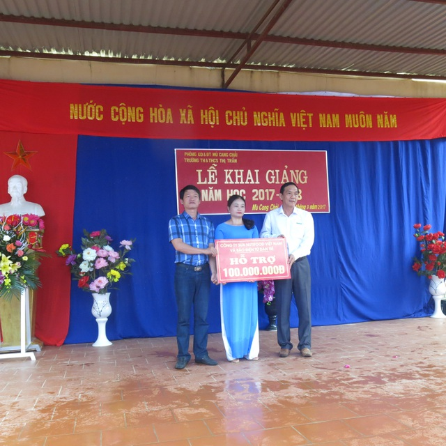 Để giúp đỡ nhà trường khắc phục các thiệt hại vì lũ quét, ông Lê Nguyên Hòa, Phó Chủ tịch HĐQT Công ty Sữa Nutifood (ngoài cùng bên phải) phối hợp với báo Dân trí đã trao 100 triệu đồng sửa chữa phòng học đến cô Phạm Thị Thủy, Hiệu trưởng Trường TH và THCS thị trấn Mù Cang Chải