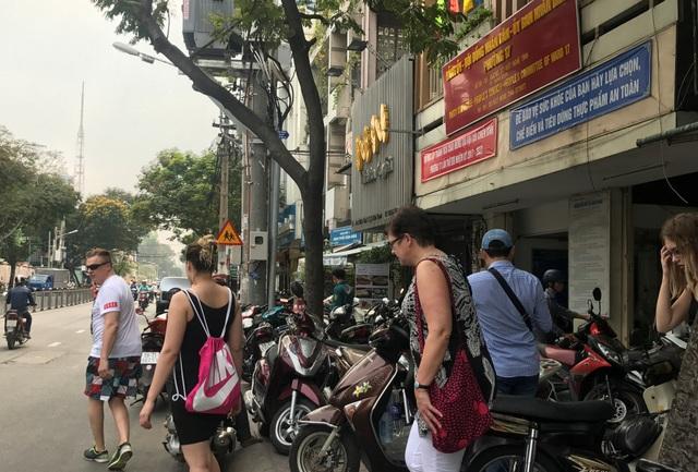 Người đi bộ, trong đó không ít du khách nước ngoài, ngán ngẩm khi buộc phải đi xuống lòng đường.